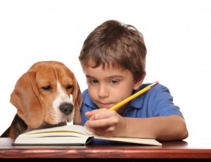 Kid doing homework with his dog